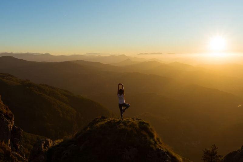 eine Frau, die sich auf dem Gipfel des Berges ausdehnt und die aufgehende Sonne betrachtet
