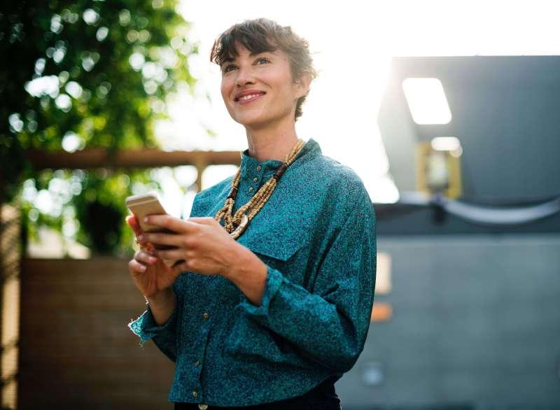 eine Frau, die in der Sonne steht und lächelt und ein Handy hält