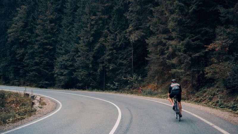ein Mann, der auf einer Straße durch einen Wald radelt
