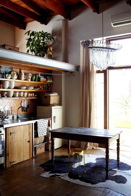 Jolie leçon de style avec cette petite cuisine de style industriel, son carrelage cuivré et ses meubles vintage en bois brut. Retrouvez plus de photos de ce loft dans l'article.