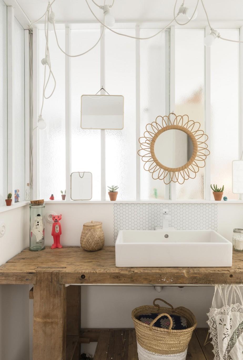 Jolie inspiration déco avec cette salle de bain lumineuse et naturelle, décorée de meubles en bois bruts et en osier. Retrouvez plus d'inspiration avec cette maison de bord de mer dans l'article.