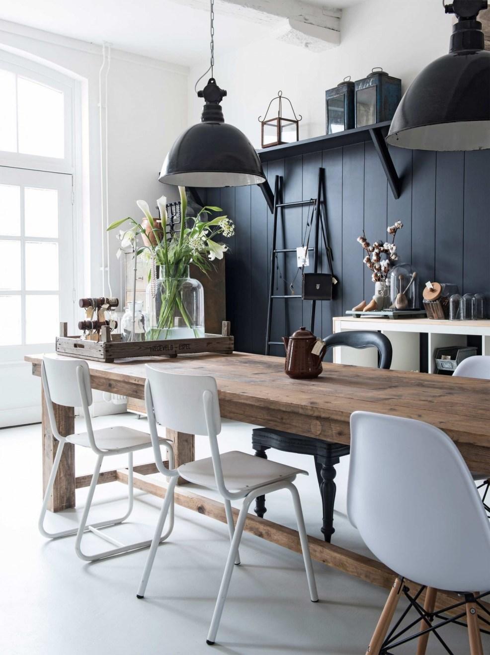 Une charmante salle à manger au style rustique et contemporain, avec sa belle table en bois brut et ses objets vintage. Retrouvez toutes les images de cette maison de campagne dans l'article !