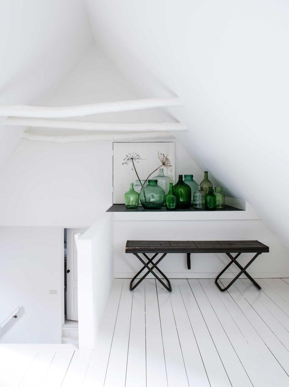 Une impressionnante collection de dame-jeanne pour décorer cette magnifique chambre sous les combles. Trouvez plus d'inspiration avec les images de cette maison rustique néerlandaise.