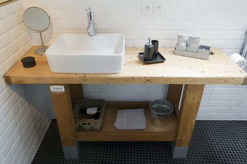 Une petite salle de bain industrielle, avec un meuble en bois brut. Retrouvez plus d'inspiration dans l'article.
