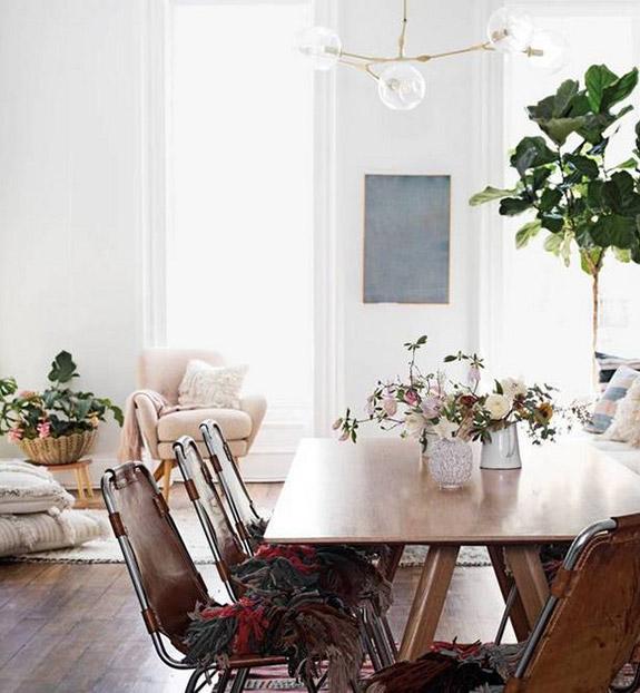 Un salon à la déco cosy et bohème, avec des chaises en cuir et des coussins ethnique, et une abondance de fleurs | salon bohème | salon bohème cosy | déco bohème chic #salleamanger #saloncosy
