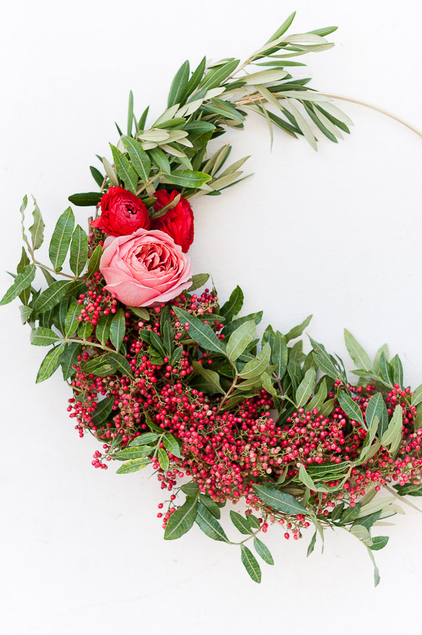 Embellisez votre intérieur avec une couronne de Noel moderne, avec son look asymétrique et ses jolies fleurs rouges