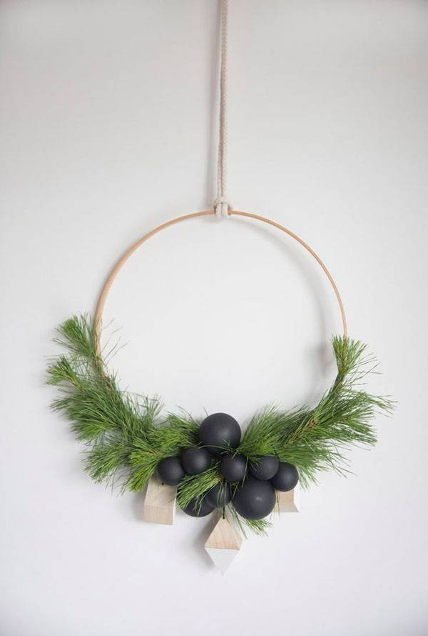 Une couronne de Noel moderne, réalisée à partir de branches de sapin et d'ornements décoratifs