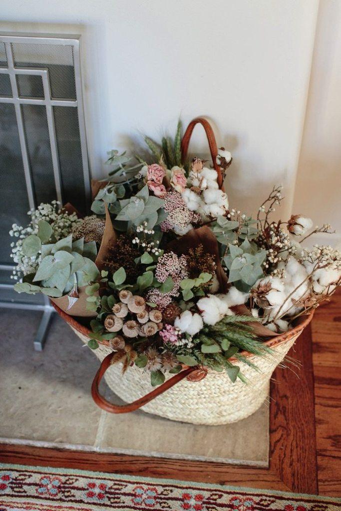 Un bouquet de fleurs séchées et d'eucalyptus dans un panier en osier