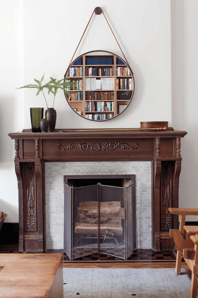 Une cheminée décorée d'un miroir rond