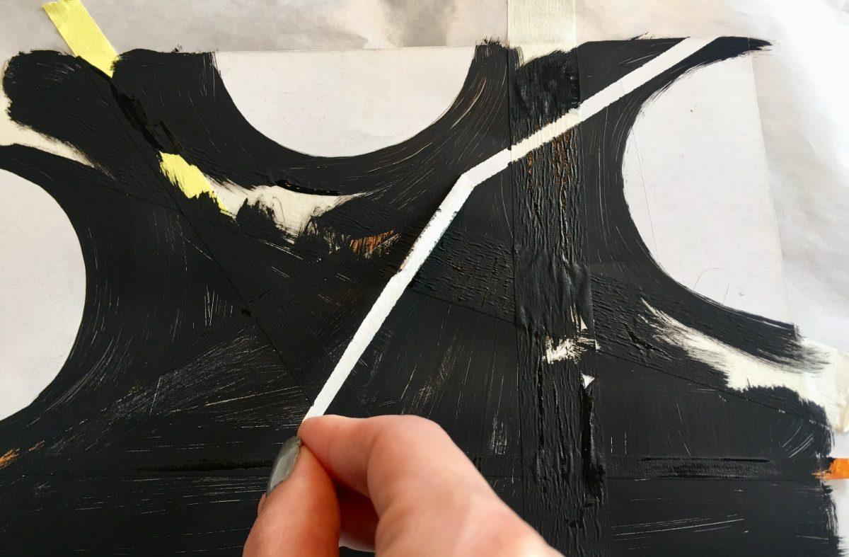 Hand peeling tape off black-painted paper