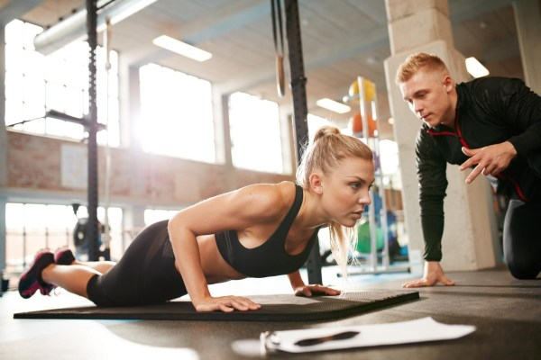 Woman doing push ups with her fitness instructor.