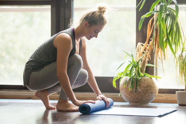 Woman rolling a workout mat.