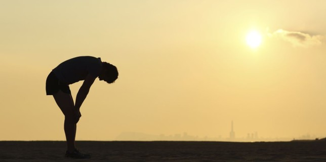 Silhouette of an exhausted runner at sunset