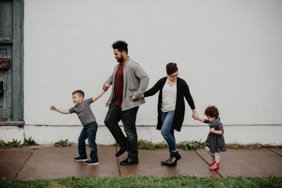 Family of four holding hands and walking down sidewalk.