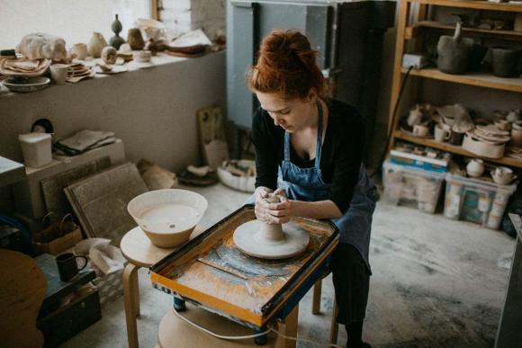 Woman using pottery wheel in workshop.