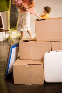 Stacked cardboard boxes in front of a child pulling at his father's shirt