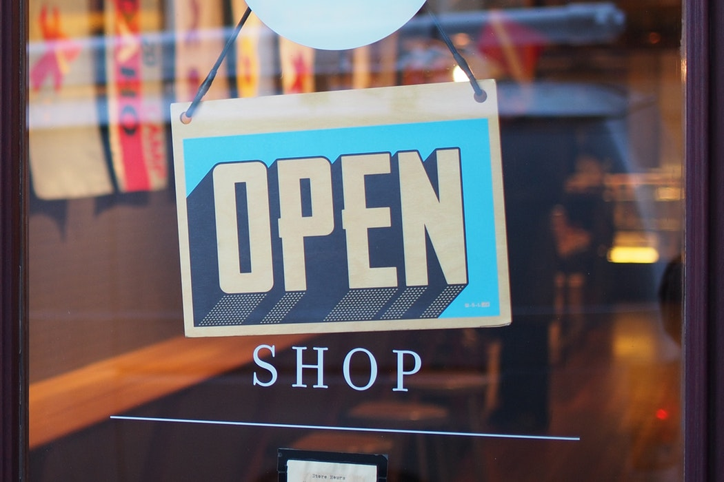 "An ""Open"" sign on a shop window."