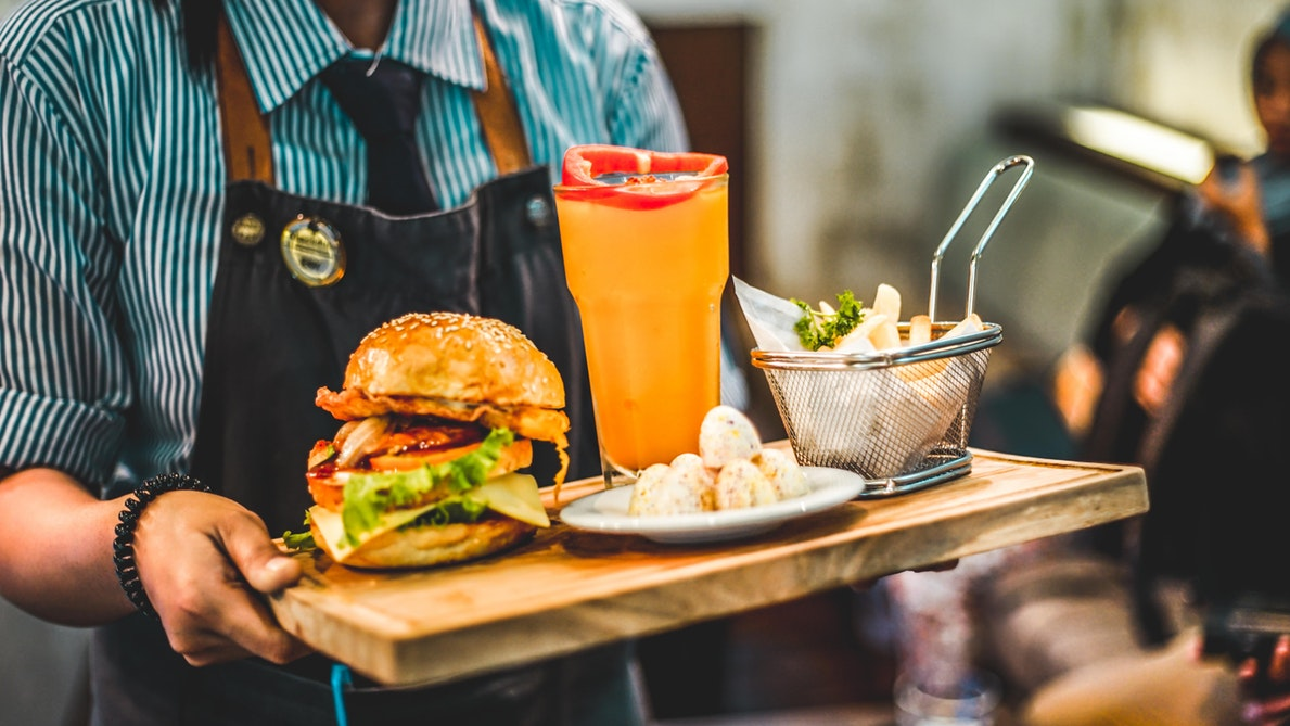 A plate with a burger, fries, and a drink.