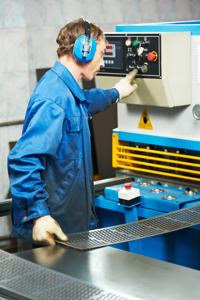 A factory worker uses a heavy machine.