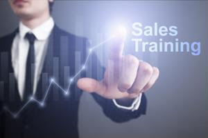 """A businessman pointing to a """"sales training"""" graphic."""