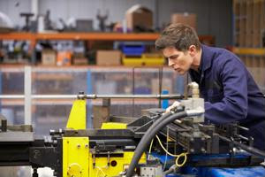 An employee uses a heavy machine on a shop floor.