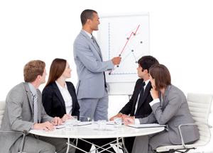 A sales team leader points to a graph.