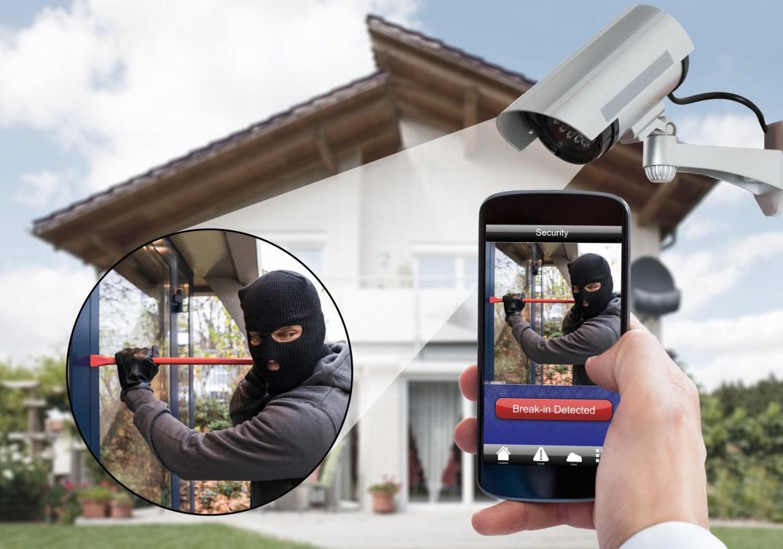 Pessoa monitorando sua casa pelo celular. Bandido assaltando casa