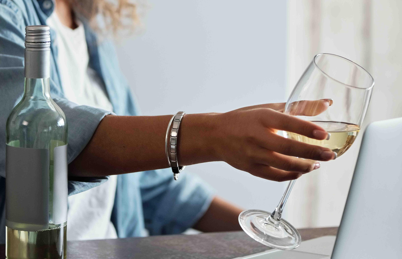Personne faisant semblant de trinquer avec son verre de vin blanc devant son écran