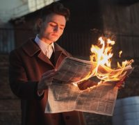 A young man reads a burning newspaper