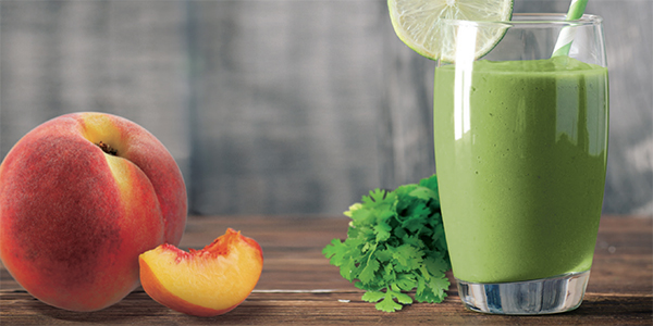 Green Smoothie on a white table next to fruit