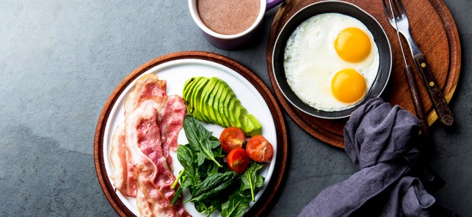 Bacon, avocado, eggs and tomato with keto coffee on a dark table and modern wooden plates with a grey linen napkin