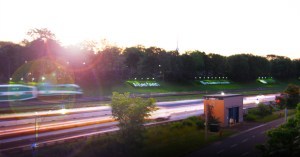 A GO train passes by corporate logos on a hill beside Toronto's Gardiner Expressway.
