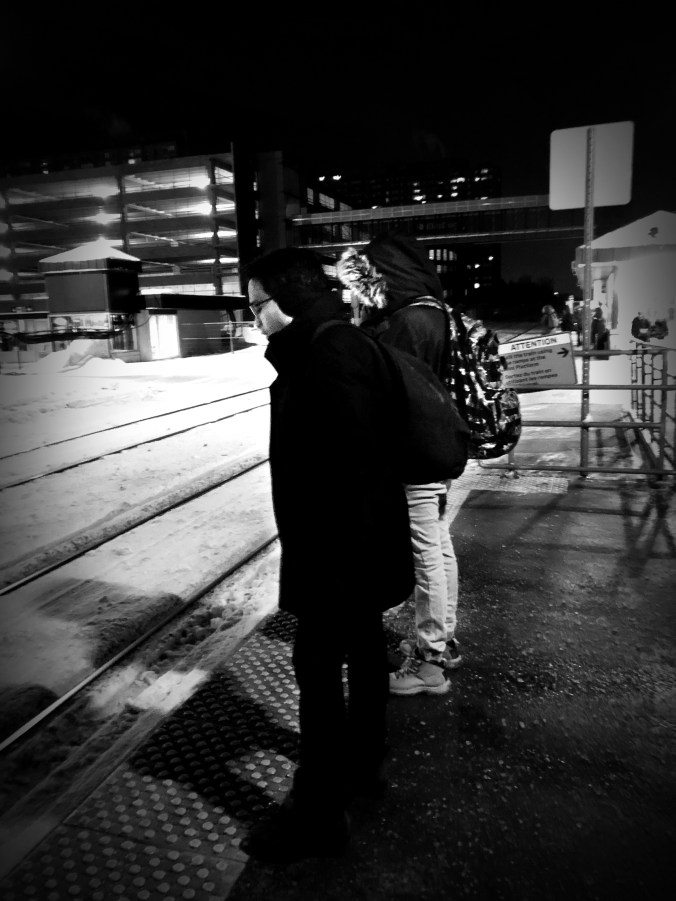 Two people stand in the cold while waiting for a train.