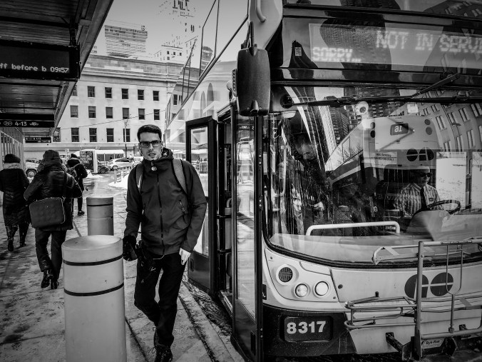 A man walks off a bus and onto a cold platform. He has headphones on and is looking at the camera. The city and buildings are behind him.