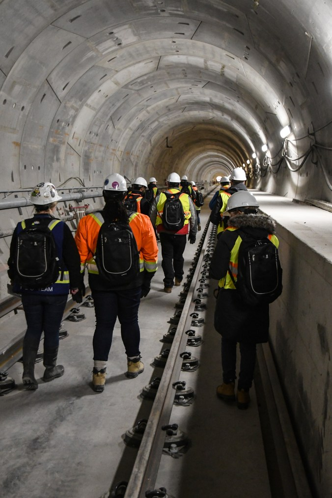 A group of people walk down through a concrete tunnel that will be part of the Crosstown LRT.