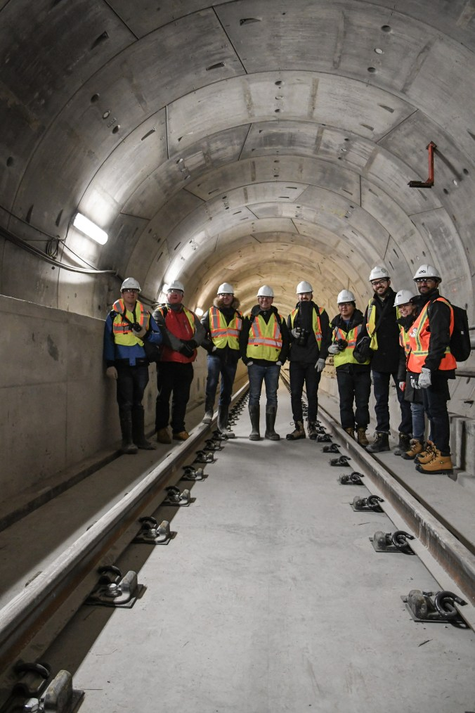 Nine people pose and look at the camera while standing on track and in a large concrete tunnel.