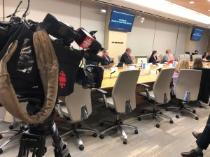 Metrolinx board members are seen around a large table. A CBC camera is in the forground.