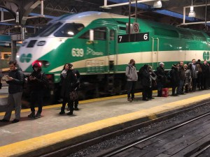 Passengers wait on the platform during rush hour as a GO train arrives.