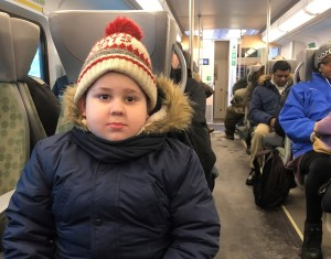 A young boy, Lucas Andrade, sits budled up in winter gear and sitting inside a GO train bound for Toronto's Union Station.