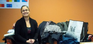 Amanda Henriques sits smiling at the camera, beside a pile of donated clothing.