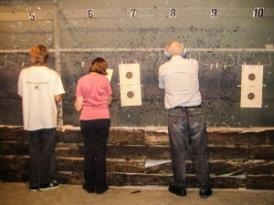 Three members of the gun club, backs to the camera, check their targets.