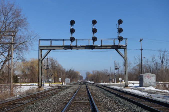 A set of three signal stands loom over rail lines, and a level crossing, on the Lakeshore East line.