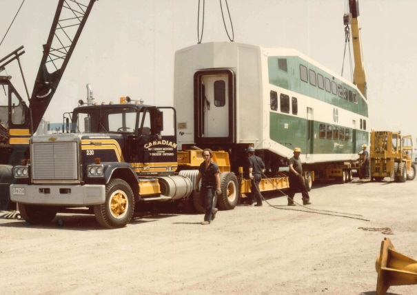 The body of a train carriage arrives at a yard on the back of a large truck. Men work to offload it.