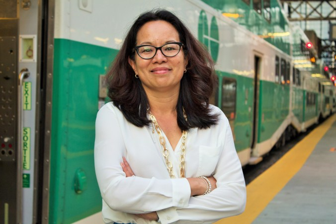 Leslie Woo poses next to a GO Train.