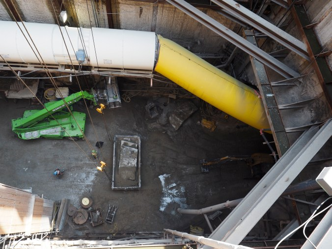 A photo shows down into a pit under construction - lots of dirt and equipment.