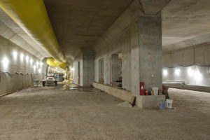 Concrete walls and yellow ventillation tubing can be seen below the surface.