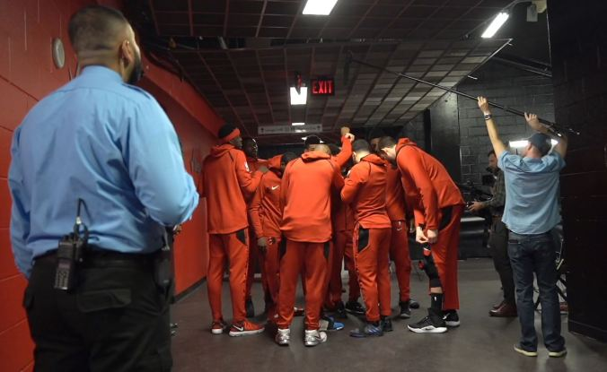 Zohaib Khan watching the Raptors players as they talk in a huddle.