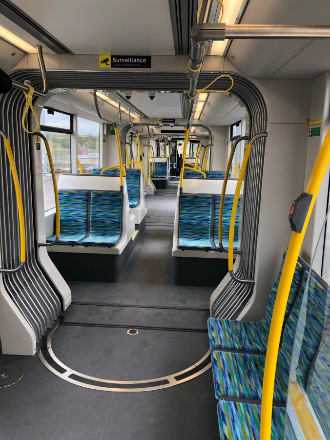 The inside of the LRV with blue and green seats and plenty of standing room.