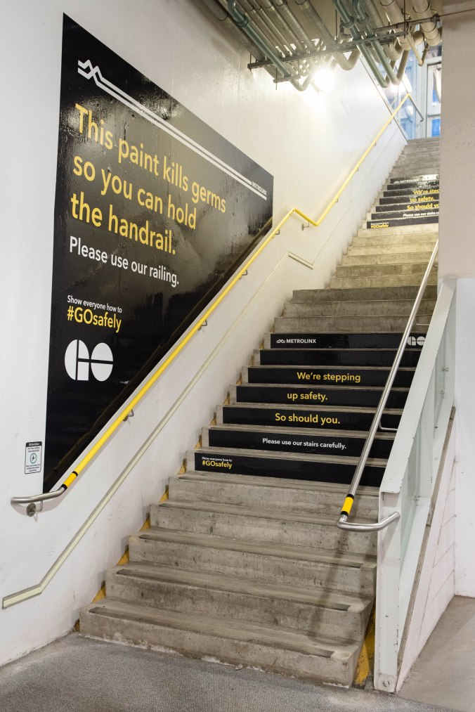 Stairs are shown with warning signs reminding customers to hold the handrails and watch their steps.