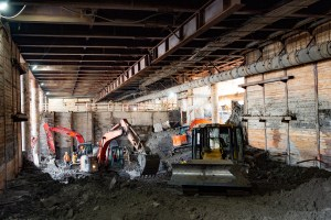 Tractors and crews work in a large pit, under a ceiling of wood and metal.